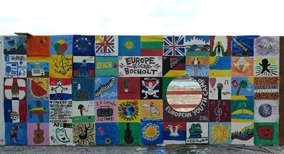 Buntes Ergebnis der Malaktion auf dem Bauzaun am Hertie-Gelände der Teilnehmerinnen und Teilnehmer am europäischen Jugendcamp