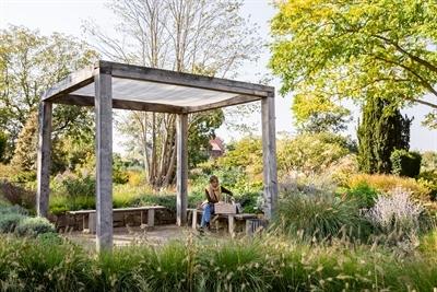 Inmitten einer Pflanzenvielfalt lädt der Kreislehrgarten Steinfurt zum Picknick ein – zum Beispiel unter dem Kubus. © Münsterland e.V./Romana Dombrowski