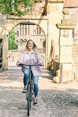 Unterwegs auf der 100 Schlösser Route gibt es viel Geschichte zu erleben. Titelbild Broschüre, Fahrradfahrerin Burg Vischering © Münsterland e.V./Philipp Fölting