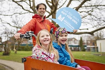 Bei der Veranstaltung gibt es wichtige Klimaschutz-Tipps - zum Beispiel Lastenfahrradfahren. Vater mit Kindern im Lastenrad © Münsterland e.V./Philipp Fölting