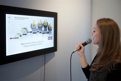 ©  - Das Foto zeigt eine Museumsmitarbeiterin, die die Karaokestation im Hoffmann-von-Fallersleben-Museums ausprobiert.