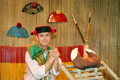 © Theater Tom Teuer - Auf dem Bild ist ein Schauspieler mit einem Torero-Hut zu sehen, der neben einer Trage steht , auf der Plüsch-Hörner befestigt sind. Er guckt traurig.