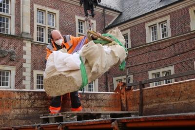 Mitarbeiter des Kreisbetriebs unterstützten die Firma Lehmkuhl Restaurierungen dabei, die Sandsteinfigur sicher ins Schloss zu befördern.