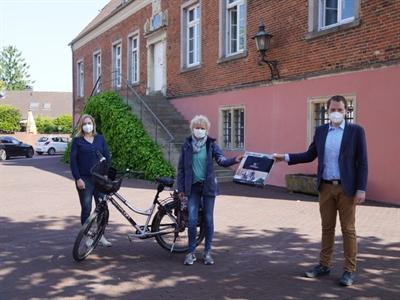 ©  - Hanna Schnetger (li.) und Bürgermeister Tom Tenostendarp bei der Übergabe des Gewinns an Sabine Terhörst.