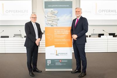 © Swaantje Hehmann - Staatssekretär Dr. Frank-Thomas Hett (links) und Oberbürgermeister Wolfgang Griesert (rechts) gratulieren der Stiftung Opferhilfe zum 20-jährigen Bestehen und begrüßen die Tagungsmitglieder im Ratssitzungssaal und an den PC-Bildschirmen.
